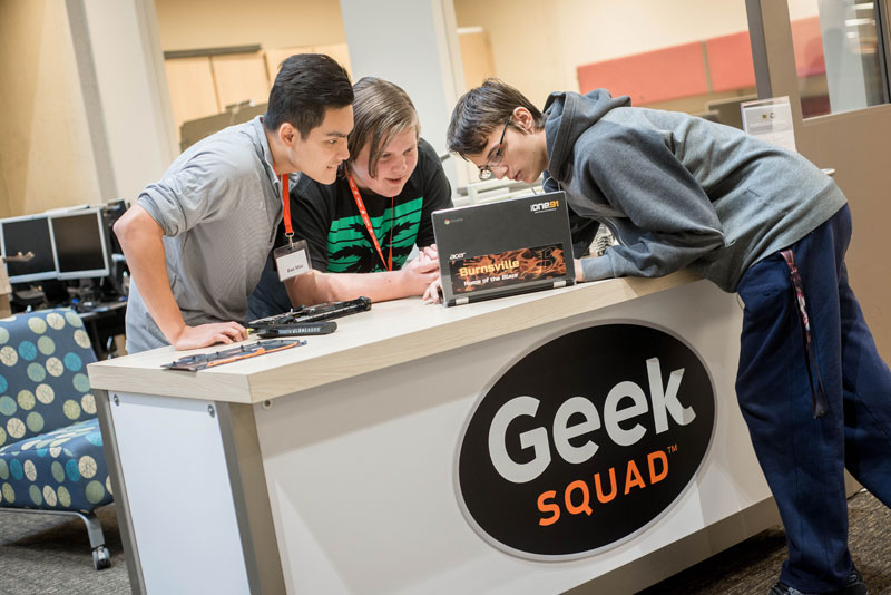 Three students study a computer at Best Buy's Geek Squad Academy